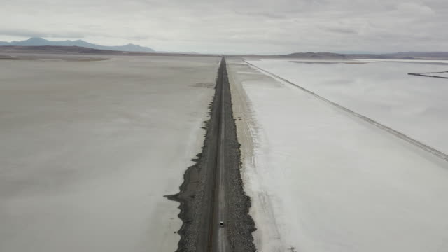vidéos et rushes de aerial pedestal shot showing dust coming from a truck driving across a remote wilderness on a dirt road, utah, united states of america - route de campagne