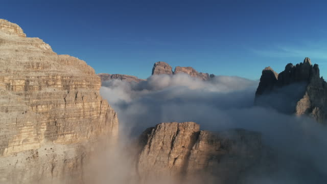 vidéos et rushes de aerial pedestal shot showing low level clouds surrounding mountains, tre cime di lavaredo, dolomites, italy - site classé au patrimoine mondial de l'unesco