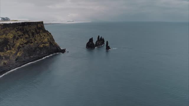 aerial pedestal shot showing off shore basalt columns, reynisfjara, vik, iceland - basalt stock videos & royalty-free footage
