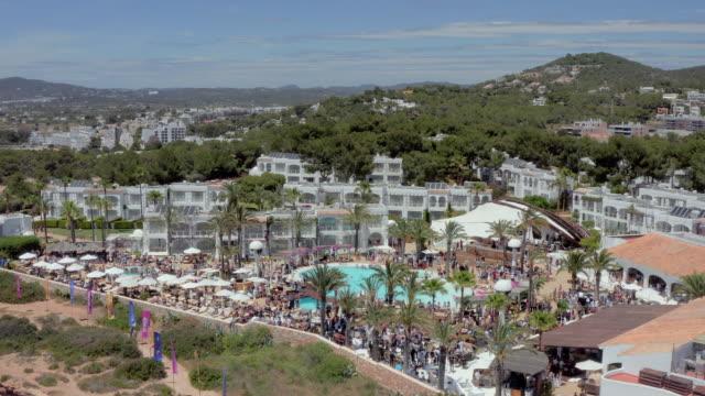 aerial: people at tourist resort with swimming pool - ibiza, spain - イビサ島点の映像素材/bロール