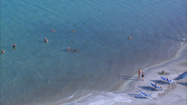 aerial people bathing and floating in the dead sea, judea desert, israel - dead sea stock videos and b-roll footage