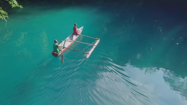 vídeos de stock, filmes e b-roll de aerial: people floating in a boat with a jungle surrounding them in espiritu santo, vanuatu - oceano pacífico