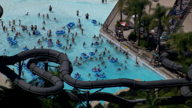aerial ts ms people in swimming pool at six flags hurricane harbor water park / valencia, california, united states.. - water slide stock videos & royalty-free footage