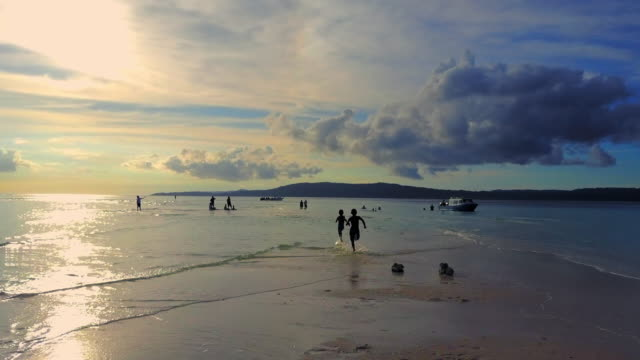 aerial: people on the beach in beautiful sunset, raja ampat islands, indonesia - awe stock videos & royalty-free footage