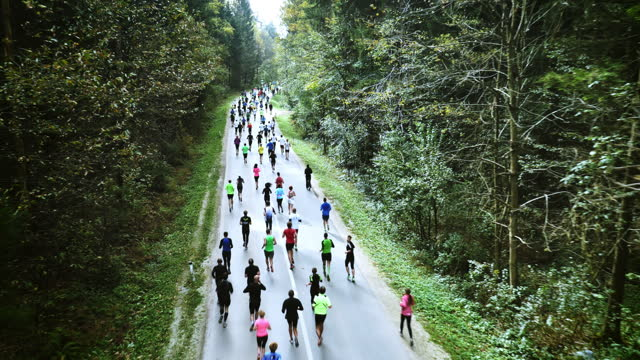 Aerial People running a marathon on countryside road through forest