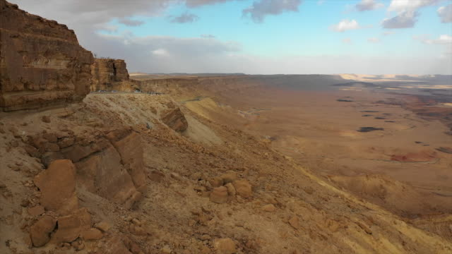 aerial: people sightseeing on the edge of a desert cliff in negev desert, israel - negev stock videos & royalty-free footage