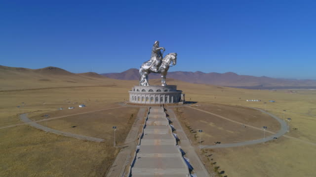aerial: people walking up the steps towards a museum with a statue of genghis kahn on top - ulaanbaatar, mongolia - top capo di vestiario video stock e b–roll