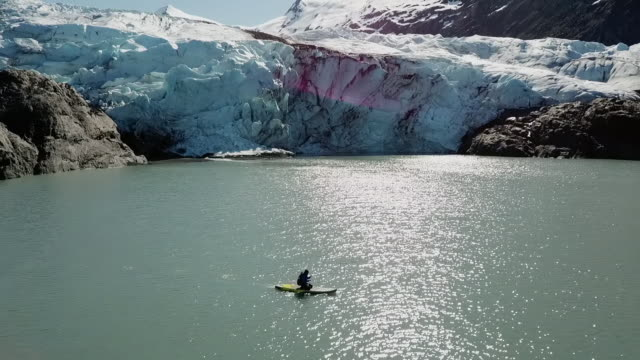 aerial: person paddleboarding near a glacier - using a paddle stock videos & royalty-free footage