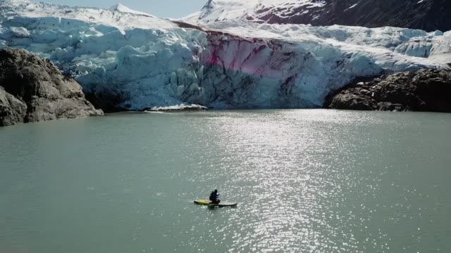 vidéos et rushes de aerial: person paddleboarding near a glacier - pagayer