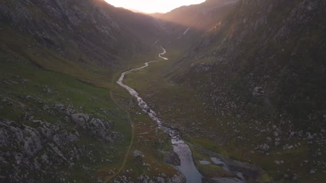 aerial perspective flying over highland mountains - twilight stock videos & royalty-free footage