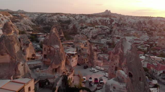vídeos de stock, filmes e b-roll de aerial perspective flying over iconic landscape at sunrise - capadócia