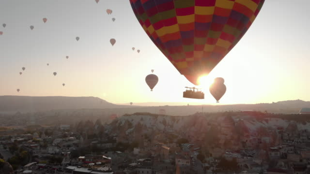 aerial perspective flying past hot air balloons at sunrise, iconic destination behind - türkei stock-videos und b-roll-filmmaterial