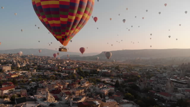 aerial perspective flying past hot air balloons at sunrise, iconic destination behind - discovery stock videos & royalty-free footage