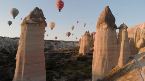 stockvideo's en b-roll-footage met aerial perspective flying past hot air balloons at sunrise, iconic destination behind - unesco world heritage site