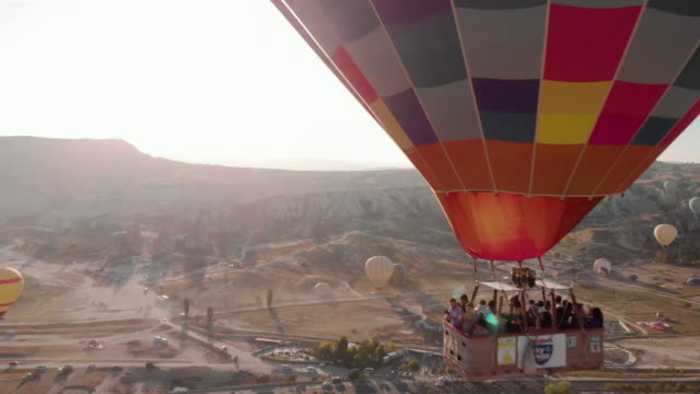 aerial perspective flying past hot air balloons at sunrise, iconic destination behind - awe stock videos & royalty-free footage