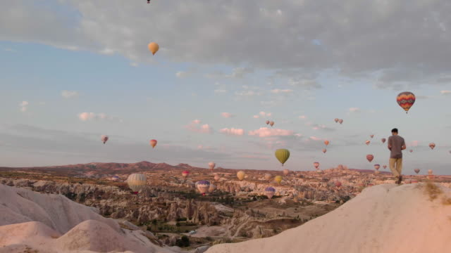 aerial perspective flying past hot air balloons at sunrise, iconic destination behind - adventure stock videos & royalty-free footage