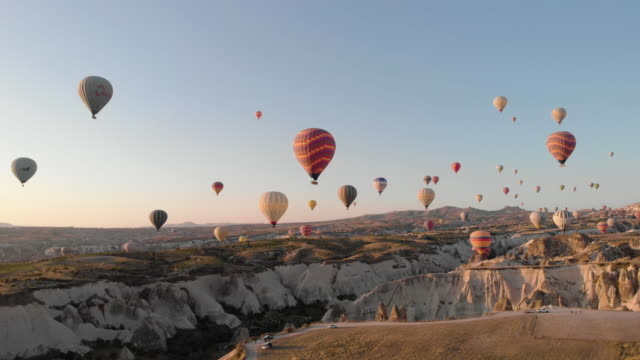 vídeos de stock, filmes e b-roll de perspectiva aérea voando através do icônico vale antigo ao nascer do sol - turquia