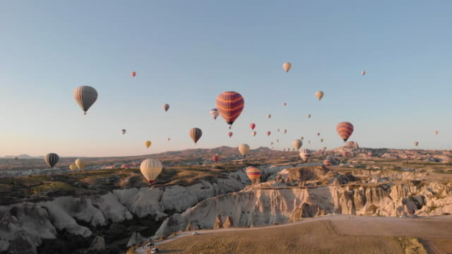 aerial perspective flying through iconic ancient valley at sunrise - hot air balloon stock videos & royalty-free footage