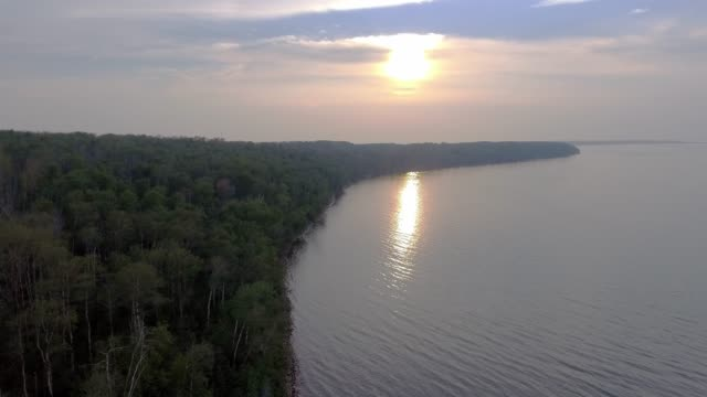 aerial perspective of a lakeshore & dock at sunset - lakeshore stock videos & royalty-free footage