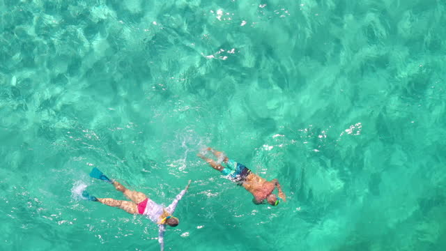 aerial perspective of mature couple snorkeling in vibrant blue water - active seniors stock videos & royalty-free footage