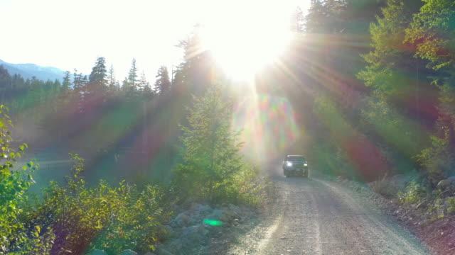 vídeos de stock, filmes e b-roll de perspectiva aérea de picape dirigindo ao longo da estrada remota da montanha - vida simples