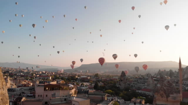 vídeos de stock e filmes b-roll de aerial perspective past minaret to hot air balloons flying over iconic landscape - variação