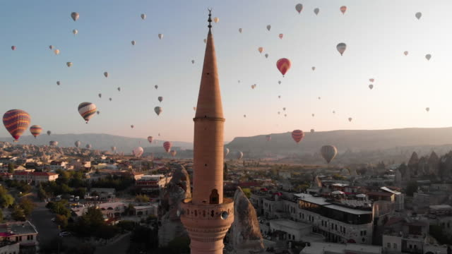 aerial perspective past minaret to hot air balloons flying over iconic landscape - minaret stock videos & royalty-free footage