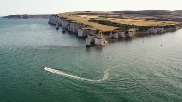 aerial perspective showing a motorboat rounding old harry rocks, dorset, england, united kingdom - rock face stock videos & royalty-free footage