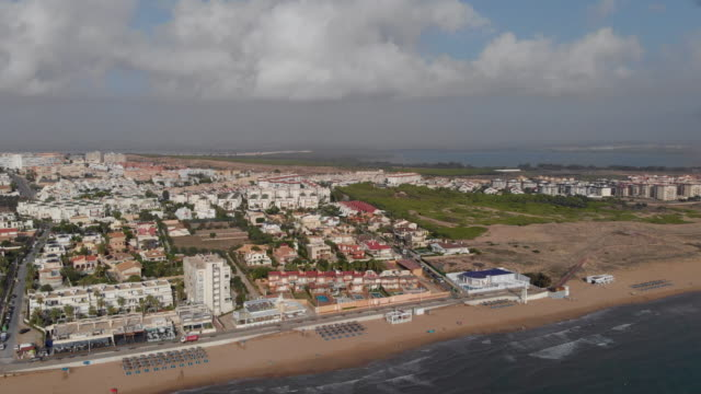 aerial photo beach parasols and sun-beds deckchairs on the sandy coastline of la mata district in torrevieja resort town - sunny video stock e b–roll