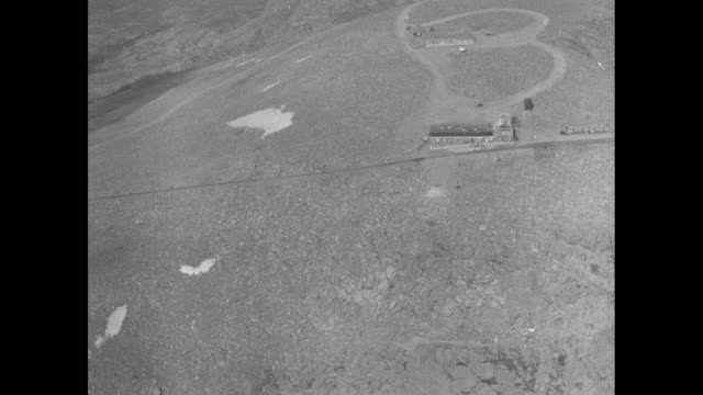 Aerial Pikes Peak plane wing in fg / aerial peak / POV from plane passing over mountain can see circles on dirt road and buildings on mountaintop /...