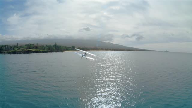 vídeos de stock e filmes b-roll de aerial plane point of view following biplane flying over pacific ocean / hawaii - ilha
