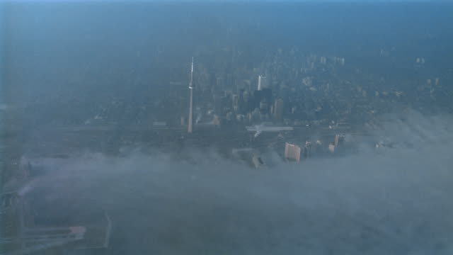 Aerial plane point of view through clouds towards CN Tower / Toronto, Ontario