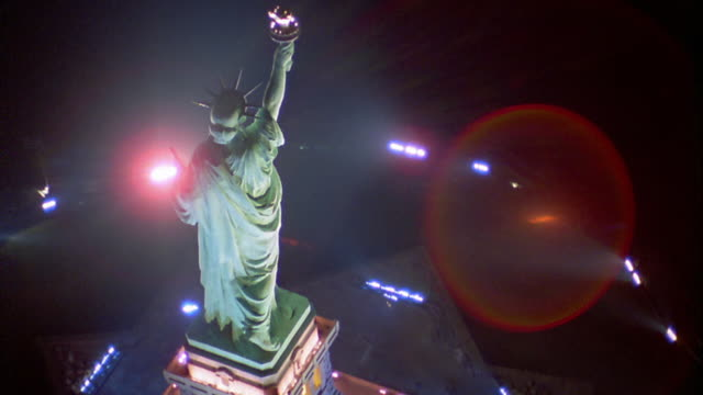 aerial point of view above and around statue of liberty at night (lens flare) / new york city - statue of liberty new york city video stock e b–roll
