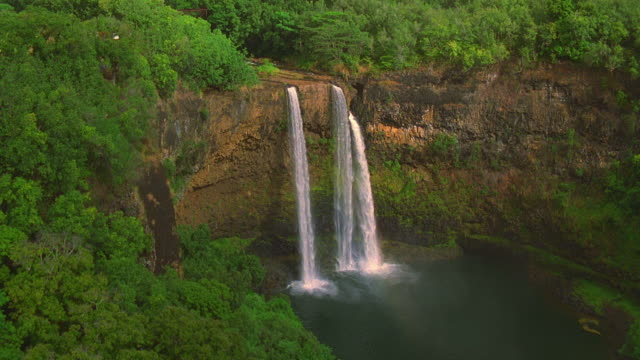 aerial point of view approaching and passing over wailua falls / kauai, hawaii - isola di kauai video stock e b–roll