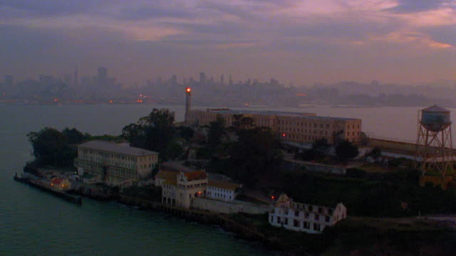 Aerial point of view around abandoned prison on Alcatraz Island in bay at sunset / San Francisco, California