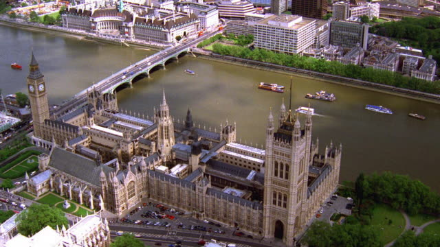 Aerial point of view around Big Ben and Houses of Parliament with boats on Thames River / London
