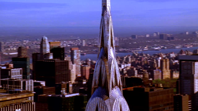 aerial point of view around chrysler building's art deco spire with met life and empire state buildings in background - chrysler building stock-videos und b-roll-filmmaterial