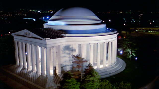 aerial point of view around lit up jefferson memorial with city lights in background at night / washington d.c. - jefferson memorial stock videos & royalty-free footage