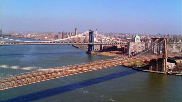 aerial point of view brooklyn and manhattan bridges w/dumbo + brooklyn skyline in background - brooklyn bridge stock videos & royalty-free footage
