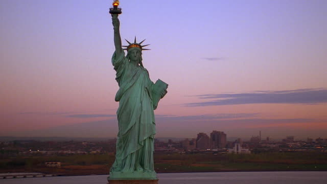 aerial point of view circling statue of liberty, ny harbor at dawn / new york city - statue of liberty new york city video stock e b–roll