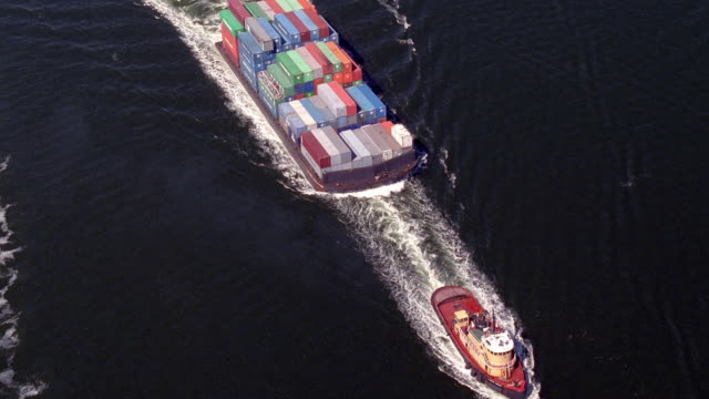 aerial point of view circling tugboat towing barge full of cargo in water - barge stock videos & royalty-free footage