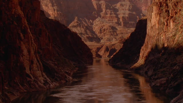 Aerial point of view dolly shot zoom out over Colorado River and through Grand Canyon / Arizona