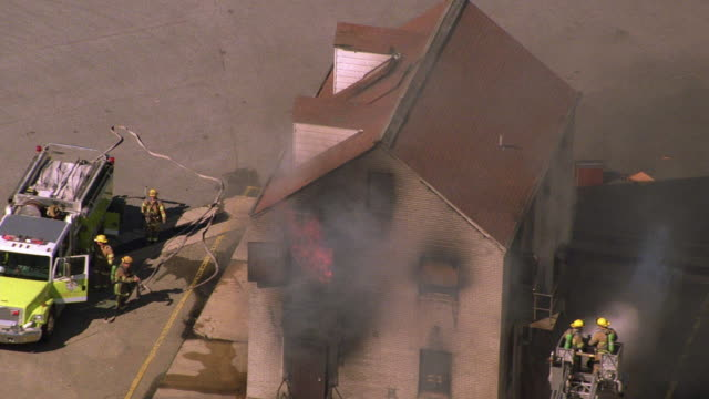 aerial point of view firemen fighting mock house fire / dragging hose and spraying water from ladder / baltimore - fire engine stock videos & royalty-free footage
