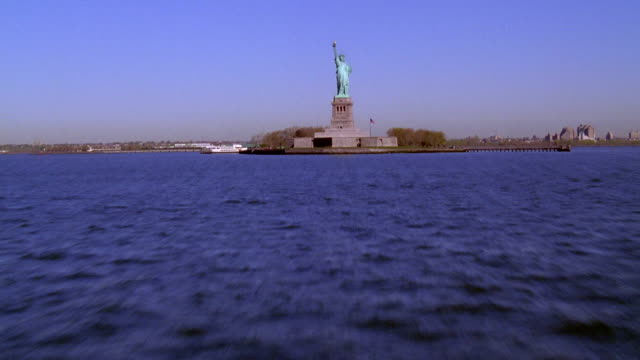 aerial point of view flying low over ny harbor toward statue of liberty+ circling her head - 1999 stock videos & royalty-free footage