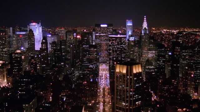 aerial point of view manhattan, met life building and grand central station at night / new york city - new york stock-videos und b-roll-filmmaterial