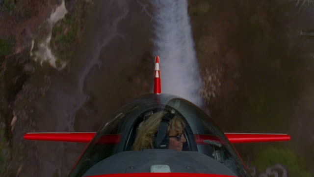 aerial point of view medium shot female pilot in cockpit of red airplane performing skywriting stunts - captain stock videos & royalty-free footage