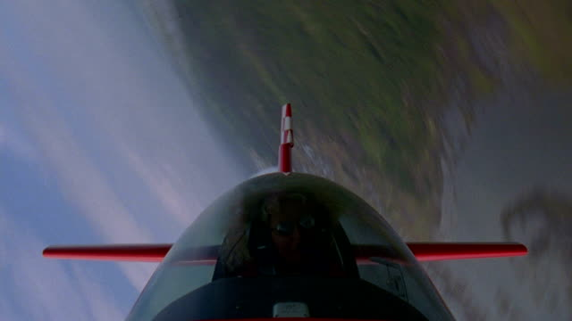 aerial point of view medium shot female pilot in cockpit of red airplane performing spiral stunts - pilot stock videos & royalty-free footage