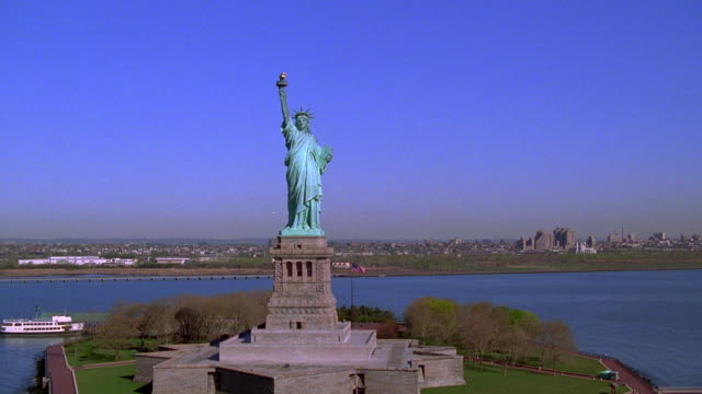 aerial point of view moving over ny harbor toward statue of liberty, circling her head - anno 1999 video stock e b–roll