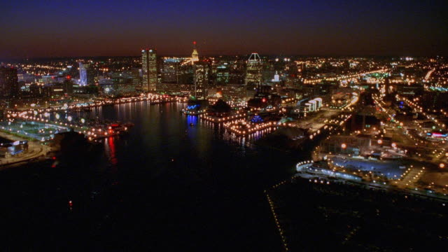 aerial point of view over baltimore harbor, towards and over downtown at night / maryland - hafen von baltimore stock-videos und b-roll-filmmaterial