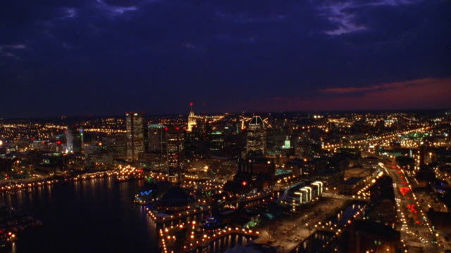 aerial point of view over baltimore harbor, towards and over downtown at night / maryland - baltimore maryland bildbanksvideor och videomaterial från bakom kulisserna